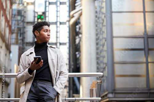 Fotografía  Fashionable young black woman standing in the city holding smartphone, low angle