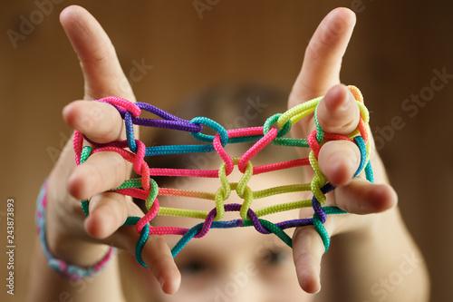 Fototapeta Girl playing classic string game, creating shapes obraz