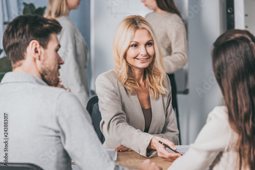 Fototapety, obrazy: smiling mature businesswoman looking at young colleagues while working together in office