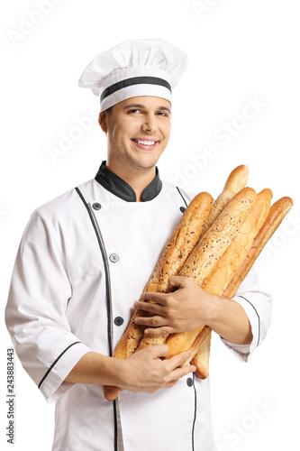 Papel de parede Young male baker holding baguette breads