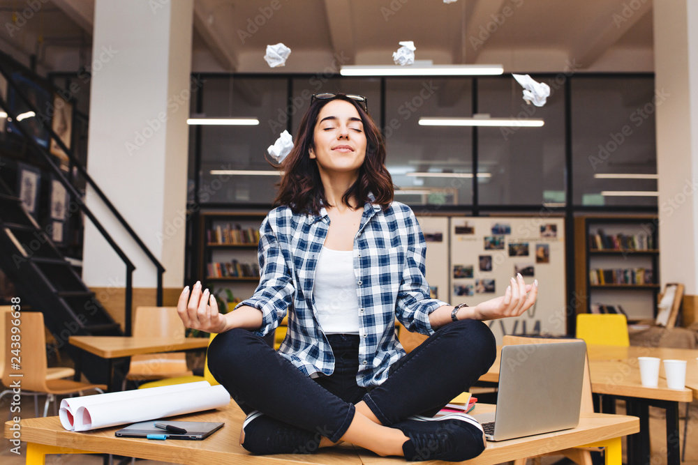 Fototapeta Young joyful brunette woman having meditation on table surround work stuff and flying papers. Cheerful mood, taking a break, at  work, studying, relaxation, smiling with closed eyes