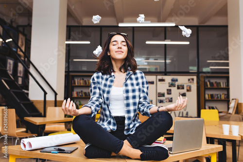Obraz Young joyful brunette woman having meditation on table surround work stuff and flying papers. Cheerful mood, taking a break, at  work, studying, relaxation, smiling with closed eyes - fototapety do salonu