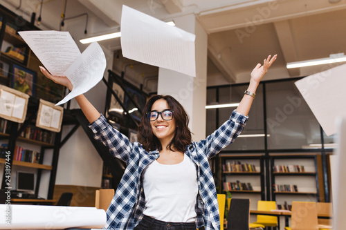 Fotografering  Joyful young brunette woman in black glasses throwing papers above in library