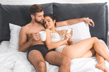 Beautiful Sexy Couple Lying With Coffee Cups In Bed At Home