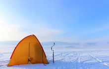 Bright Yellow Tourist Tent And Drill For Winter Fishing On The Ice-covered Empty Lake. Helping Fishermen To Escape From Bad Weather. Ice Fishing In The Winter In Siberia. Landscape In Frosty Morning