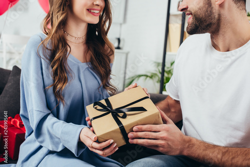 Photo  cropped view of young happy couple holding gift box with ribbon