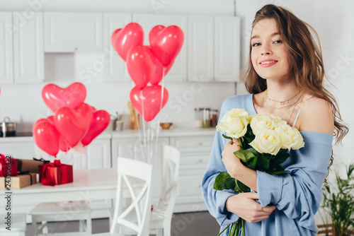Photo  selective focus of a smiling girl holding bouquet of flowers in room decorated w