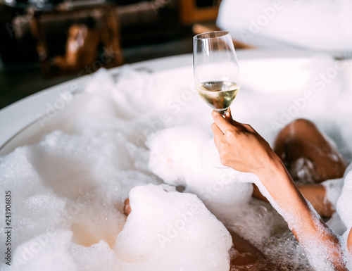 Photo Young woman relaxing in the hydro massage bath covered in foam