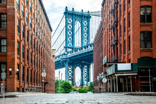 fototapeta na ścianę Manhattan Bridge between Manhattan and Brooklyn over East River seen from a narrow alley enclosed by two brick buildings on a sunny day in Washington street in Dumbo, Brooklyn, NYC
