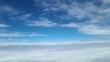 View from the window of the plane at the white clouds in the sky