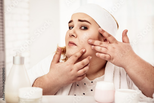 Fotografie, Obraz  Precious overweight woman checking condition of her skin