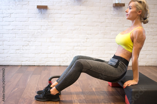 Fotografie, Obraz  Side view of an athletic blonde woman trainer doing aerobic class with fitness stepper