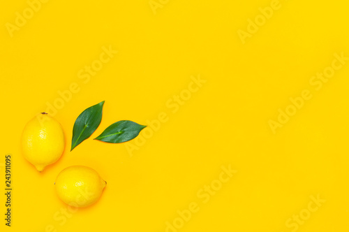 Ripe juicy lemons and green leaves on bright yellow background. Lemon fruit, citrus minimal concept, vitamin C. Creative summer food minimalistic background. Flat lay, top view, copy space.