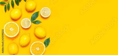 Keuken foto achterwand Vruchten Ripe juicy lemons, orange and green leaves on bright yellow background. Lemon fruit, citrus minimal concept, vitamin C. Creative summer minimalistic background. Flat lay, top view, copy space.