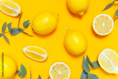 Ripe juicy lemons and green eucalyptus twigs on bright yellow background. Lemon fruit, citrus minimal concept. Creative summer food minimalistic background. Flat lay, top view, pattern
