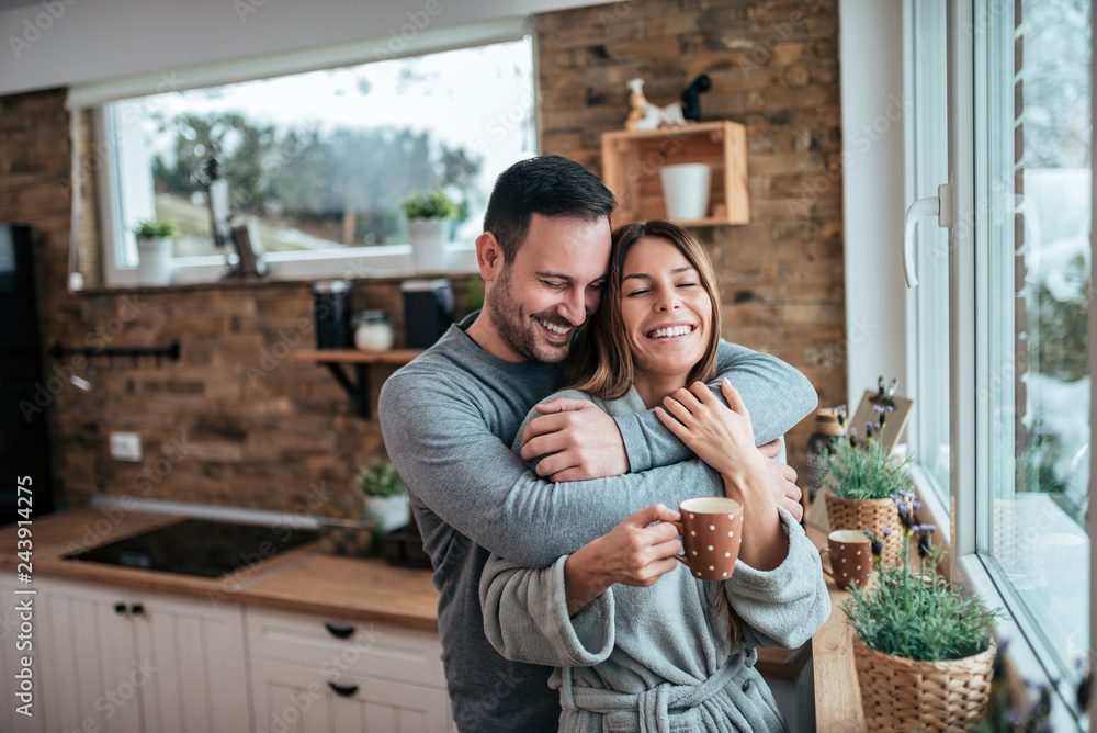 Fototapety, obrazy: Beautiful couple hugging at the kitchen in the winter morning.