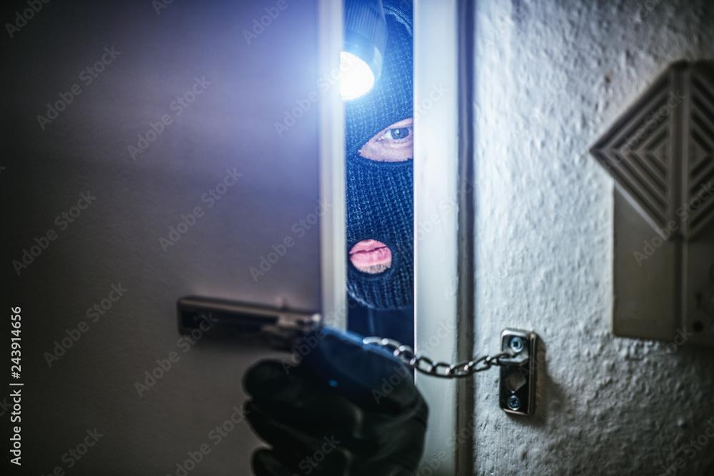 Fototapeta burglar with torch opens door of appartment