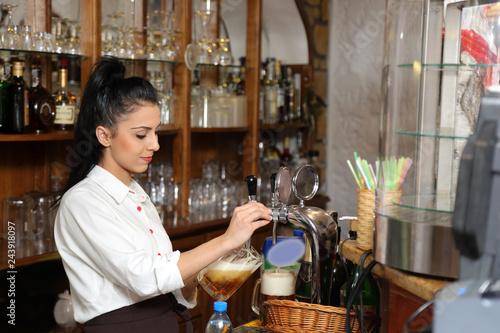 Piękna dziewczyna, barmanka leje piwo do kufla, w restauracji. Wallpaper Mural