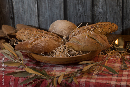 Fotografía  Artisan breads in a basket with wooden background