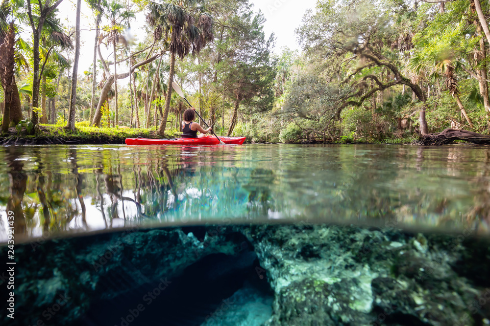 Fototapety, obrazy: Over and Under picture of a girl kayaking in a lake near an underwater cave formation. Taken in 7 Sisters Springs, Chassahowitzka River, Florida, United States of America.