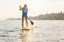 Strong, Healthy Woman Paddleboarding. Women's Outdoor Adventure Summer Water Sports.