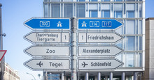 Signposts With Arrows Show The Main Directions Of Berlin, Germany. Blue Sky And Building Background.