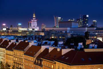 Fototapeta Warszawa Warsaw, Poland - August 11, 2017: Beautiful panoramic night view over the roofs of the Old Town to the Center of Warsaw, the Palace of culture and science (PKiN), modern skyscrapers and Krakowskie Prz