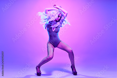 Party Sexy fashionable girl in sparkle bodysuit dance. Music vibrations, Night Clubbing. Young Gorgeous model woman with long purple hair in colorful Neon mixed light