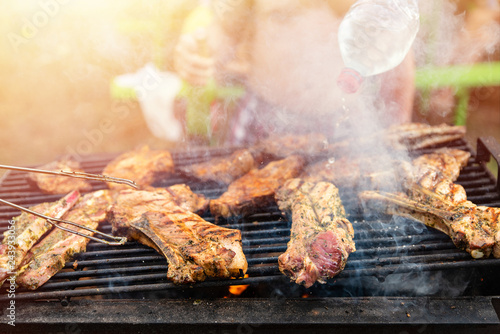 Tuinposter Grill / Barbecue Friends frying the meat ribs and steaks, process close up. Barbecue on open air, weekend rest