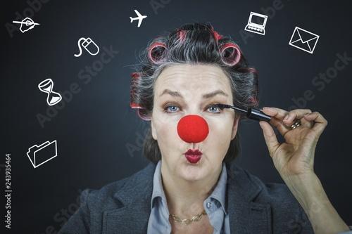 Foto  Frau mit roter Clownsnase, roten Lockenwickler, tuscht sich die Wimpern, und hat viele Dinge im Kopf, die es zu organisieren gilt