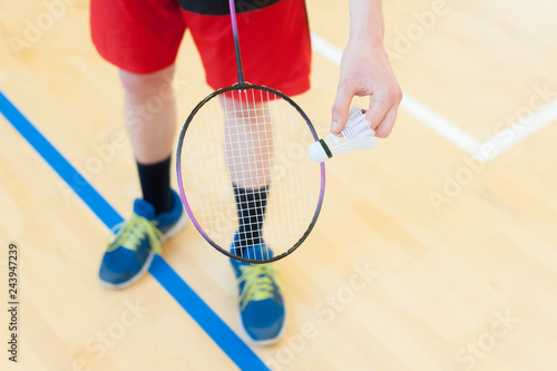 Fotografia  Man is holding the shuttlecock and the badminton racket