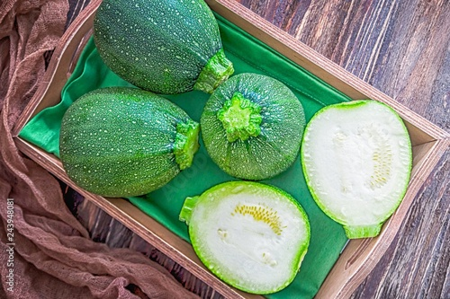 Round green zucchini or courgette on a wooden background