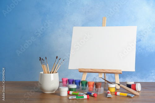 Wooden easel with blank canvas board and painting tools for children on table near color wall. Space for text