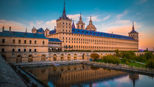 Sunset Behind The Beautiful El Escorial Palace And Monastery At The San Lorenzo De El Escorial With The Frailes Garden And Reflections In The Pond. Famous Kings Residence Near Madrid In Spain