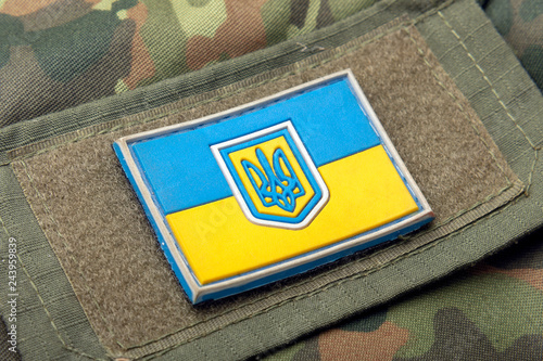 Photo  Ukrainian flag on the background of a camouflage military jacket and combat bullets