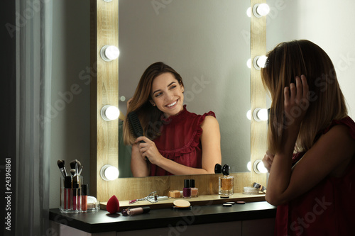Fotomural Woman brushing hair near mirror with light bulbs in dressing room