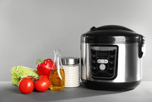 Modern Multi Cooker And Products On Table Against Grey Background. Space For Text