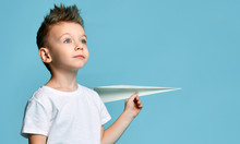 Young Baby Boy Kid In White T-shirt Hold Paper Plane Origami Smiling Looking Up On Light Blue