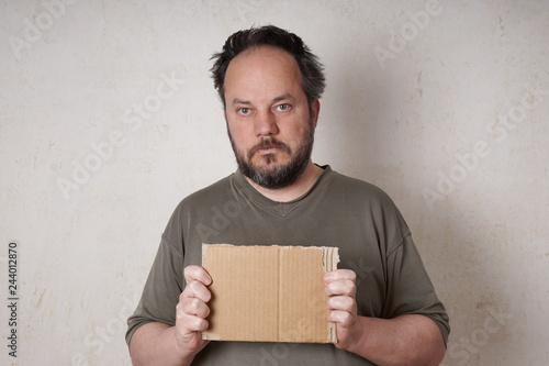 Fényképezés grubby scruffy man holding blank cardboard sign
