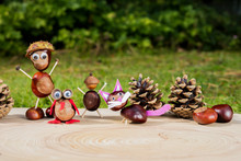 Group Of Character Or Figurines Made With Chestnuts On A Wooden Background In A Sunny Day
