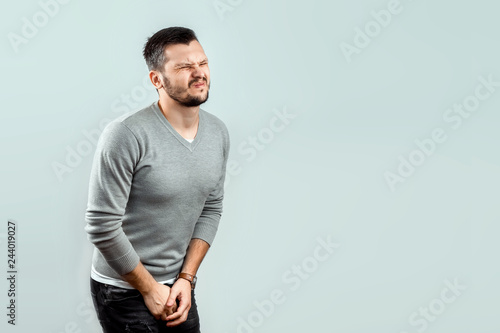 Fotografia  A young, attractive man feels pain in his groin, arms folded between his legs