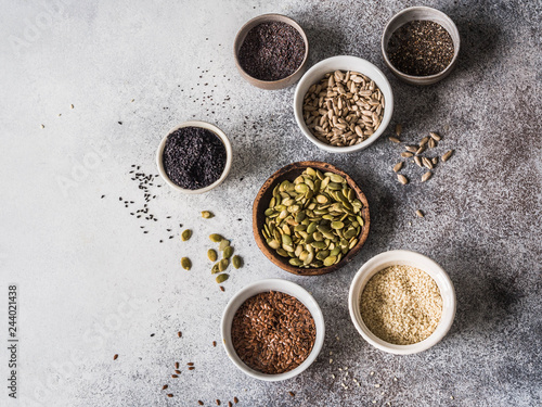 Various seeds - sesames, flax seed, sunflower seeds, pumpkin seed, poppy, chia in bowls on a gray background. Copy space. top view