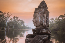 Stone Asura On Causeway Near South Gate Of Angkor Thom In Siem Reap, Cambodia. Beautiful Sunset Over Ancient Moat In Background. Angkor Thom Is A Popular Tourist Attraction.