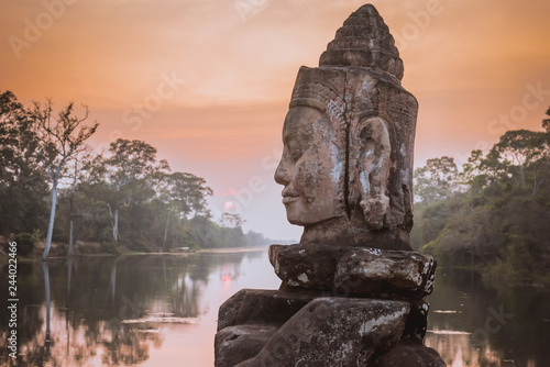 Fotobehang Historisch geb. Stone Asura on causeway near South Gate of Angkor Thom in Siem Reap, Cambodia. Beautiful sunset over ancient moat in background. Angkor Thom is a popular tourist attraction.