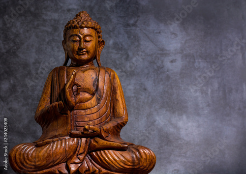 Fotografia  Wooden made buddha on a grey stone background