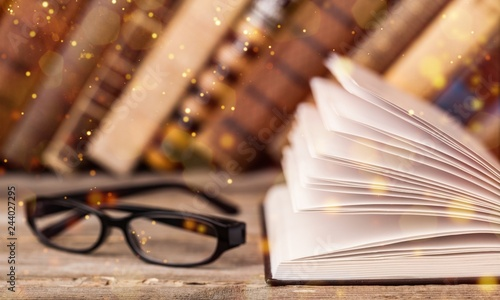 Fotografía  Open book and glasses on wooden table
