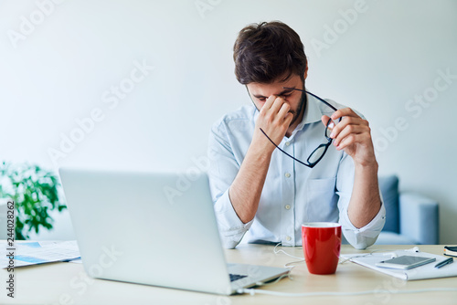 Fotografía  Young businessman having headache while working in home office