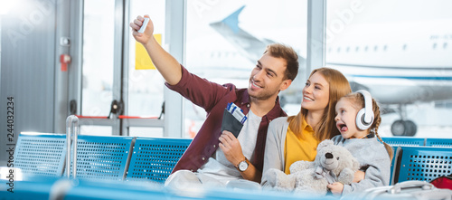 Fotografia  cheerful dad taking selfie and smiling with wife and daughter showing tongue in
