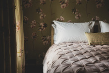 Interior View Of Bedroom With Curtains And Wallpaper With Floral Pattern, Pale Pink Quilt And White Pillows On Double Bed.