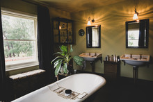 Interior View Of Bathroom With Black Mirrors Over Two Victorian Wash Stands, Sash Window And Roll Top Bath With Brass Bath Caddy.